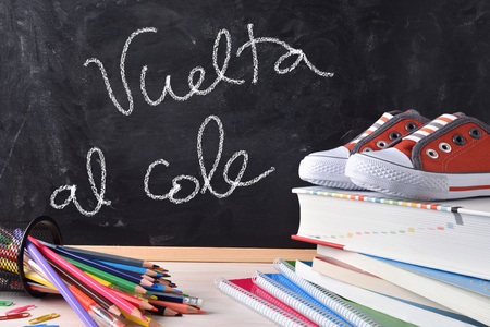 Back to school concept. Vuelta al cole written with chalk on a blackboard and school supplies and sneakers. Front view Stock Photo