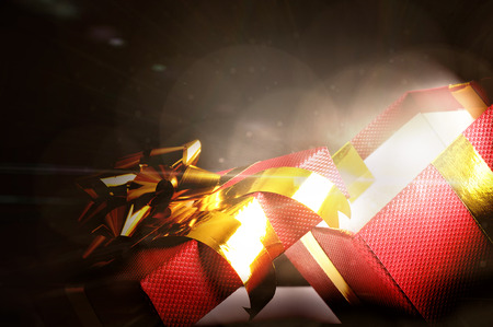 radiance: Red gift box with golden ribbon open background with glow and radiance in the dark. Close up front view.