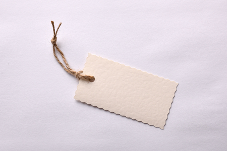 string top: Beige textured paper tag with string tied on white background. Top view Stock Photo
