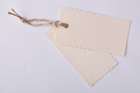 string top: Two beige textured paper tags with string tied on white background. Top view Stock Photo