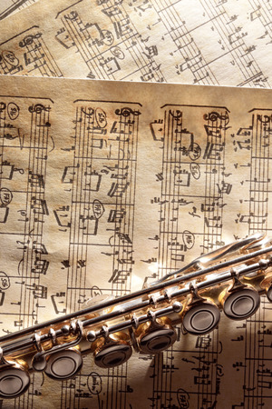 transverse: Transverse flute in the bottom on old handwritten sheet music. Vertical composition. Top view Stock Photo