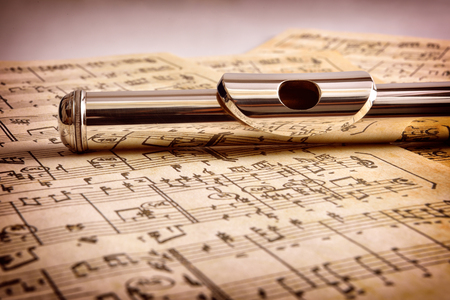 Mouthpiece of flute on old handwritten sheet music close up. Horizontal composition. Front view Foto de archivo