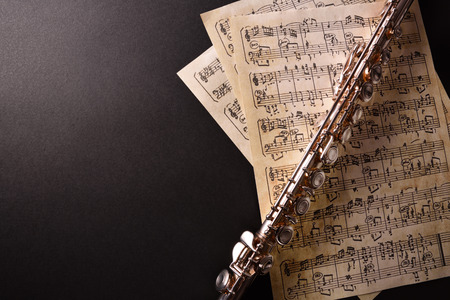 transverse: Transverse flute and old sheet music on black table. Horizontal composition. Top view Stock Photo