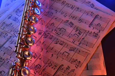 transverse: Transverse flute and old sheet music on black table red blue illuminated. Horizontal composition. Elevated view Stock Photo