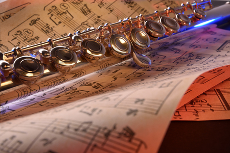 transverse: Transverse flute and old sheet music on black table red blue illuminated. Horizontal composition. Front view
