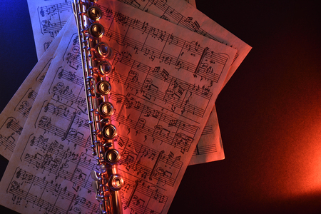 transverse: Transverse flute and old sheet music on black table red blue illuminated. Horizontal composition. Top view Stock Photo