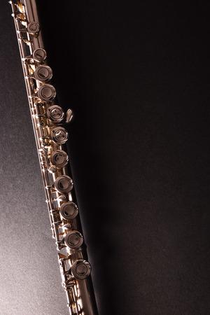 Détail de la flûte traversière sur table noire. Composition verticale Vue de dessus