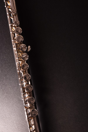 Detail of tansverse flute on black table. Vertical composition. Top view