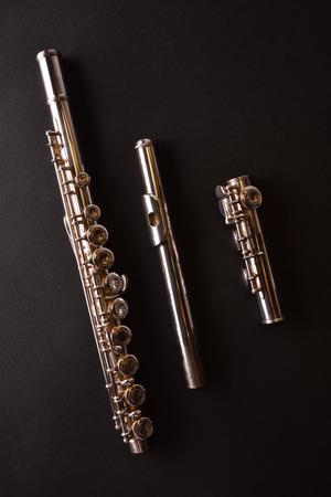 Détail de la flûte traversière démontée en trois parties sur table noire. Composition verticale Vue de dessus Banque d'images