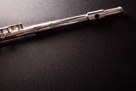Top et porte-parole de tansverse flûte sur la table noire. Composition horizontale. vue de dessus