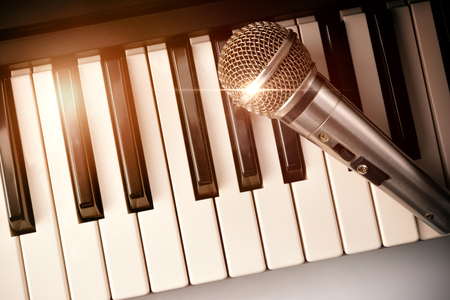 Piano and microphone with golden sparkles. Horizontal Composition.Top view Standard-Bild
