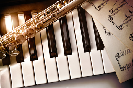 Piano and flute with golden shine and sheet music. Horizontal Composition.Top view
