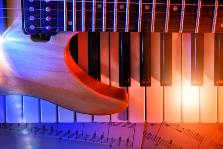 Electric guitar and synthesizer on sheet music with red and blue lights. Horizontal composition. Top view