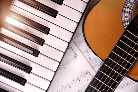 Piano and guitar with shine and sheet music background. Horizontal Composition.Top view Stock Photo
