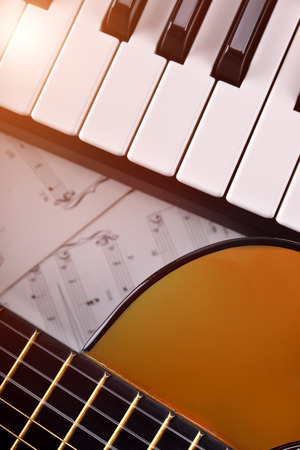 Piano and guitar with shine and sheet music background. Vertical composition.Top view Stock Photo