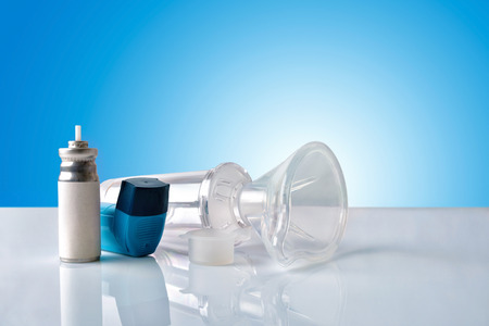 Cartridge, blue medicine inhaler, inhalation chamber and silicone mask on white glass table with blue gradient background. Front view. Horizontal composition
