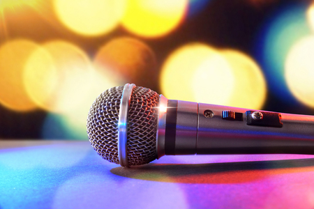 Microphone on black table and colored lights background. Front view. Horizontal composition.