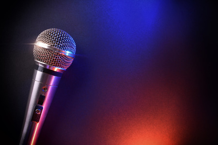 scenical: Microphone on black table with red and blue lights. Top view. Horizontal composition.