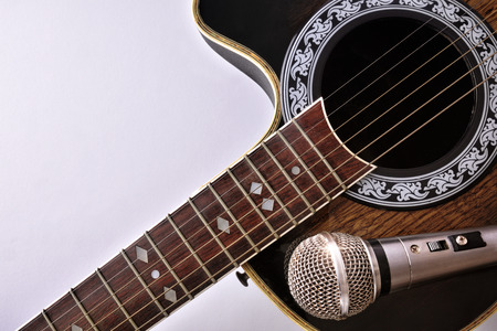 Acoustic guitar and microphone isolated on white table. Top view. Horizontal composition. Stock Photo