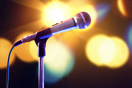 scenical: Microphone on microphone stand with cable and lights in the background. Front view. Horizontal composition.