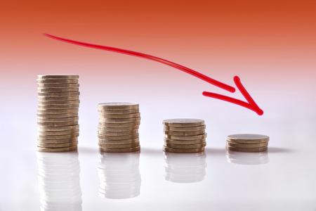 ビジネスの下向きのグラフは白い反射テーブル上のコインを表され、オレンジ色のトーンのバック グラウンドの低下します。水平方向で構成。フロ