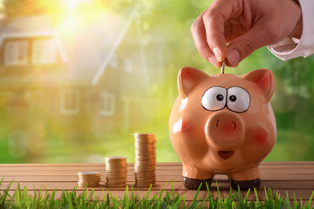 Concept savings with hand putting money into a piggy bank saving to buy a house. Objects on wooden table and nature and house background with bokeh. Horizontal composition. Front view.
