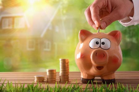 Konzept Einsparungen mit der Hand Geld in ein Sparschwein setzen ein Haus zu kaufen. Objekte auf Holztisch und Natur und Haus Hintergrund mit Bokeh. Horizontale Zusammensetzung. Vorderansicht. Standard-Bild
