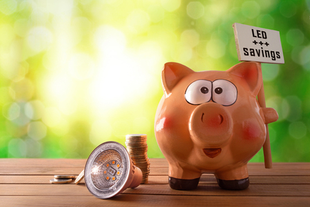 Concept of energy saving and efficiency with led bulb, coins and piggy bank with les savings banner on wooden table and nature background with bokeh. Horizontal composition. Front view.