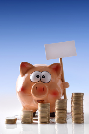 reflective: Concept savings with piggy bank with blank billboard and stacked coins on reflective white glass table and blue gradient background. Vertical composition. Front view.