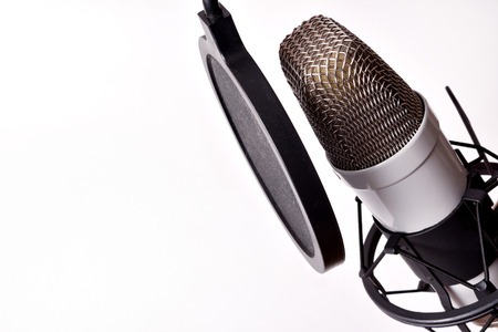 Close up studio condenser microphone with pop filter and anti-vibration mount isolated white. Elevated view Archivio Fotografico