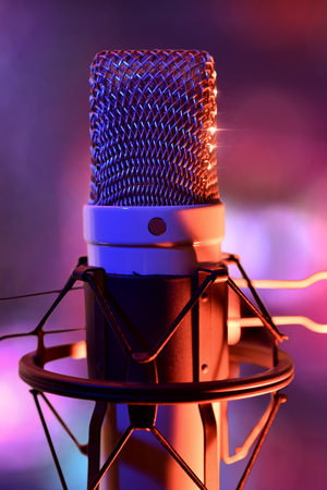 Close up studio condenser microphone on stand and anti-vibration mount.  Live recording with colored lights background. Front view. Vertical composition.