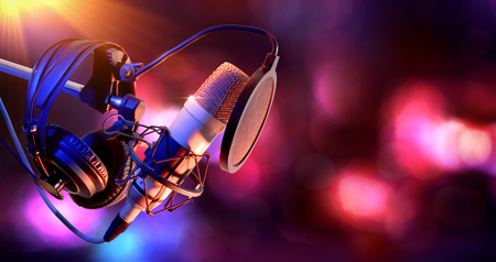 Close up studio condenser microphone with pop filter and anti-vibration mount live recording with color lights background. Side view