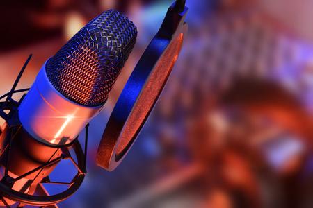 スタジオ ヘッドフォンとマイクとミキサーの背景に青、赤、本番を点灯します。昇格を表示