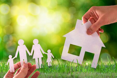 Home and family concept with paper house and family with nature background. Horizontal composition