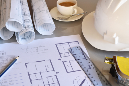 architect drawing: Working table of a construction engineer with plan of project close up. Blueprints and tools background. Top elevated view. Horizontal composition. Stock Photo