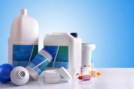 Productos químicos de limpieza para el agua de la piscina en la mesa blanca y fondo azul. Composición horizontal Vista frontal Foto de archivo