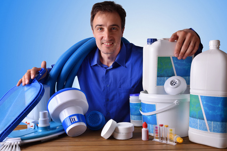Zwembadonderhoud commercieel met chemische schoonmakende producten en hulpmiddelen op houten lijst en blauwe achtergrond. Horizontale samenstelling. Vooraanzicht