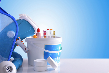 Chemical cleaning products and tools for pool water on white table and blue mosaic background. Horizontal composition. Front view Stock Photo