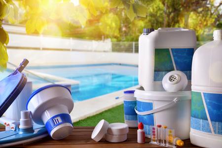 Swimmingpoolservice und -ausrüstung mit chemischen Reinigungsmitteln und -werkzeugen auf hölzernem Tabellen- und Poolhintergrund. Horizontale Zusammensetzung. Vorderansicht