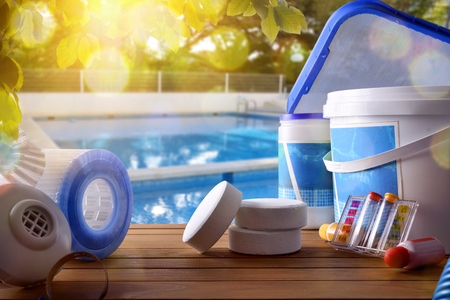 Zwembaddienst en uitrusting met chemische schoonmakende producten en hulpmiddelen op houten lijst en poolachtergrond. Horizontale samenstelling. Vooraanzicht
