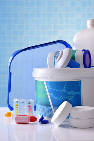 Chemical cleaning products for pool water on white table and blue mosaic background. Vertical composition. Front view
