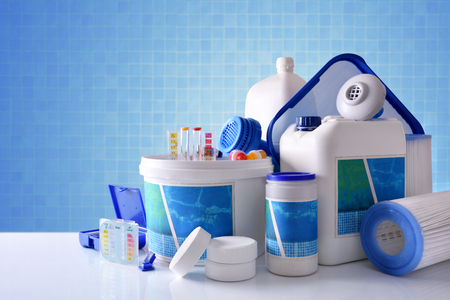 Chemical cleaning products for pool water on white table and blue mosaic background. Horizontal composition. Front view