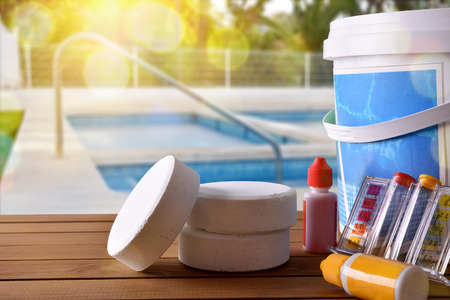 Swimming pool service and equipment with chemical cleaning products and tools on wood table and pool background. Horizontal composition. Front view Imagens - 77971812