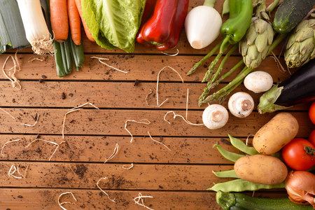 Assortment of vegetables arround a wood table. Horizontal composition. Top view