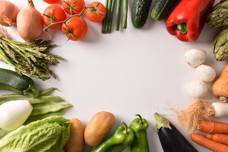 Assortment of vegetables around a white table. Horizontal composition. Top view