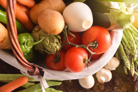 Assortment of vegetables in a wicker basket on soil. Horizontal composition. Top view Stock Photo