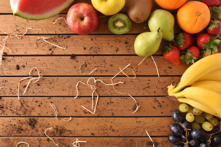 Assortment of fruits around a wooden table. Horizontal composition. Top view