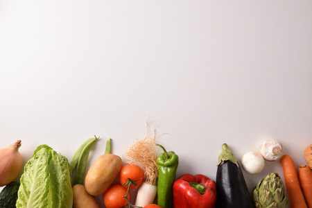 Assortment of vegetables lined up on a white table. Horizontal composition. Top view