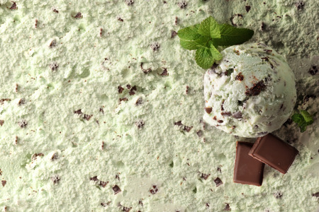 Ice cream flavored mint choco texture background with ball. Garnished with mint leaves and chocolate squares. Top view. Horizontal composition. Standard-Bild