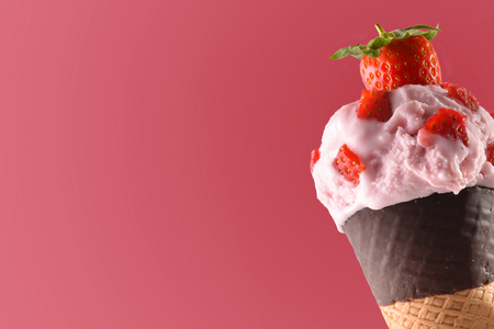 cornet: Ice cream cone flavored strawberry close up. Garnished with Strawberry pieces. With pink background. Horizontal composition. Stock Photo